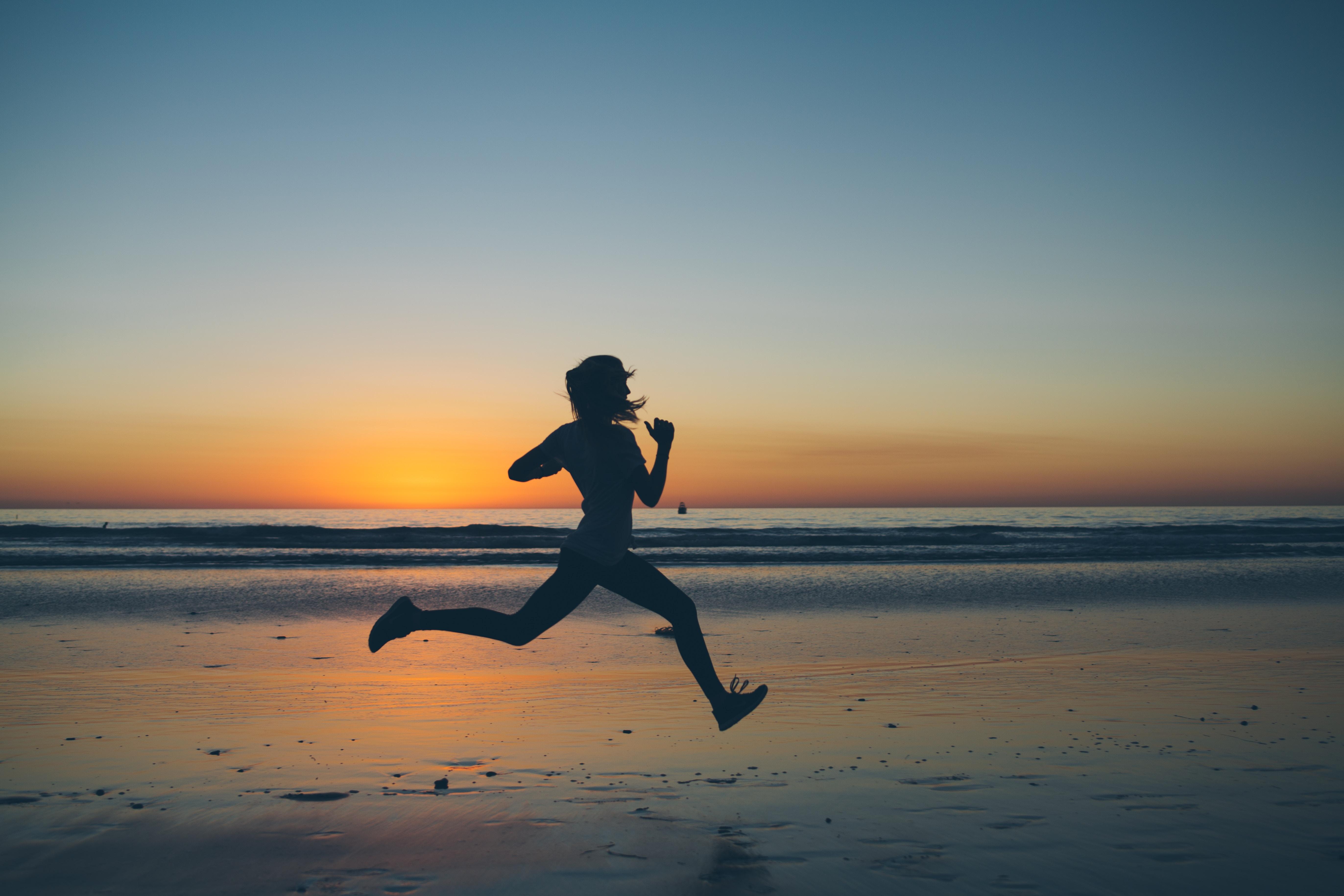 En löpare på stranden i soluppgången.