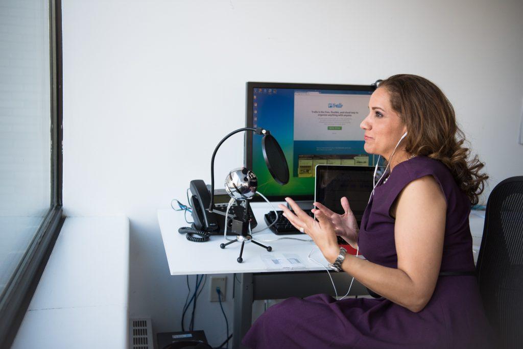 En engagerad facilitator i färd med att kommunicera med och leda deltagare på distans framför mikrofon och datorskärm.